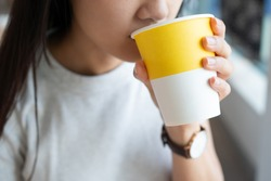 Close up of the Asian lady holding the hot drink paper cup with one hand and sipping the hot beverage