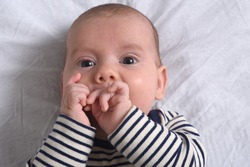 close up of the baby who plays with his hands until he sucks his finger