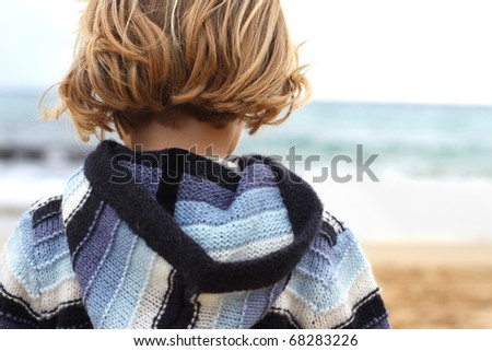 Close up of the back of a little girl facing the sea