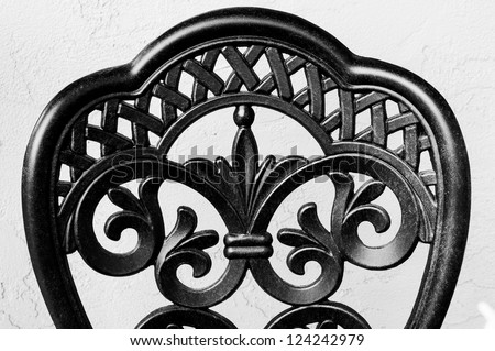 Close up of the back of a wrought iron chair in black and white against a grey stucco wall.