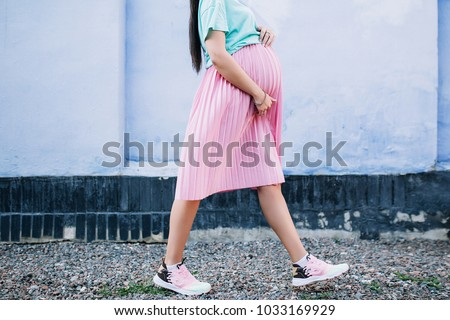 close-up of the belly and legs of a pregnant stylish girl in a pink skirt and mint shirt that goes against a blue wall background #1033169929