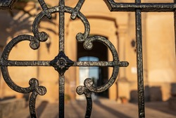Close-up of the black metal grille at the main entrance of the Municipal Cemetery of Porreres, island of Mallorca, Spain. In the background, the entrance to the cemetery out of focus