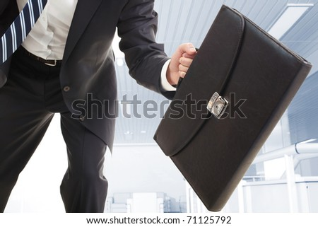 Close-up of the briefcase held by running businessman