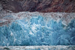 Close-up of the calving glacier wall in Tracy Arm Fjord, Alaska. Vivid blue ice on wall face. White and grey topping. Geological rock at rear. Icebergs. Dramatic colouring. Awe inspiring.