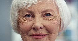 Close up of the Caucasian old happy and cheerful lady with grey short hair looking straight to the camera and smiling. Indoor.