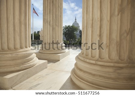 Close up of the columns  of the Supreme Court building with an American flag and the US Capitol in the background Foto stock ©