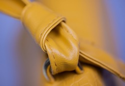 Close up of the cord of a yellow leather handbag. Woman bag macro photo. Knotted gimp of luxury fashioned bag. Fashion concept , top view with blue background. Girls  hand bag, twisted leather string
