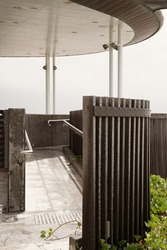 Close up of the curved architectural design of timber posts on an outdoor beachfront viewing platform