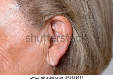 Close up of the ear of an elderly woman with her blond ear tucked back behind the ear to expose the lobe