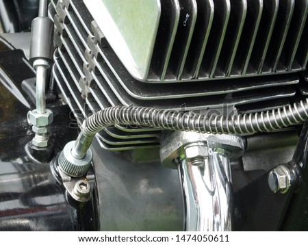 close up of the engine block of a vintage black motorcycle with shiny metal cylinder head and chrome pipes #1474050611