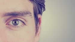 Close up of the eye and ear of a man looking straight ahead showing eyebrow, eyelash, iris, and pupil detail on a graduated grey background with copyspace. With retro filter effect.