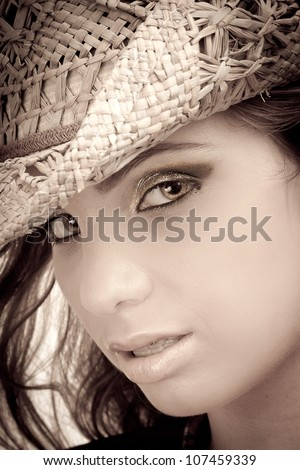 Close up of the face of a sexy young woman looking in a sensual manner. The girl is blonde and she is isolated on white background. Wearing a cowboy hat. - stock photo