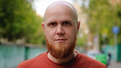 Close-up of the face of a young brutal guy with a bald head and a red beard with a serious face looking at the camera. Calm emotion. Summer evening.