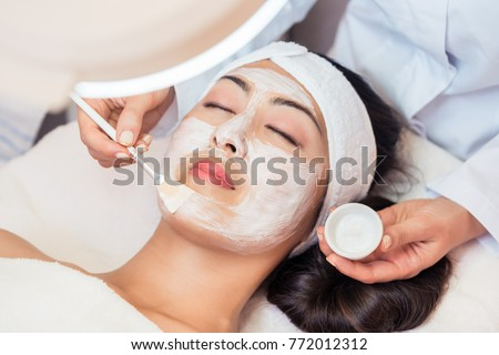 Close-up of the face of a young woman, relaxing under the gentle touch of the specialist applying on her cheeks white facial mask with rejuvenating effects