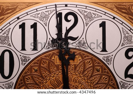 Close-up of the face of an old clock showing the time of one minute before twelve.