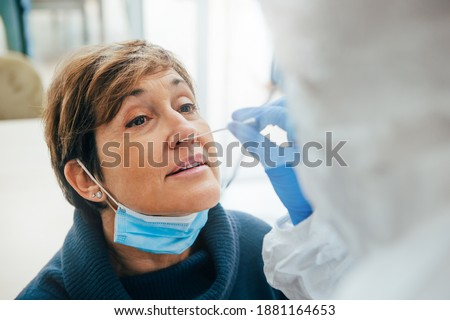 Close up of the face of senior female patient being tested for Covid-19 with a nasal swab, by a health Professional protected with gloves and PPE suit. Rapid Antigen Test during Coronavirus Pandemic.