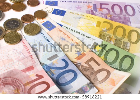Close-up of the fan of 5, 10, 20, 50, 100, 200 and 500 Euro banknotes and coins. Isolated on a white background