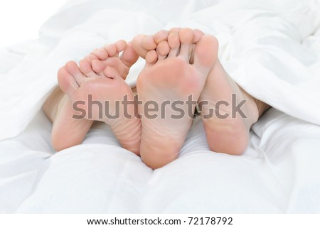 Close-up of the feet of a couple on the bed. Isolated on white background