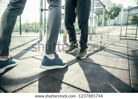 Close up of the feet of two sportsmen standing opposite each other at the sports ground while having their training outdoors