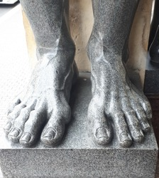 Close-up of the fingers of the sculpture stands on the stone. Granite legs sculptures of Atlantes in St. Petersburg. Russia.