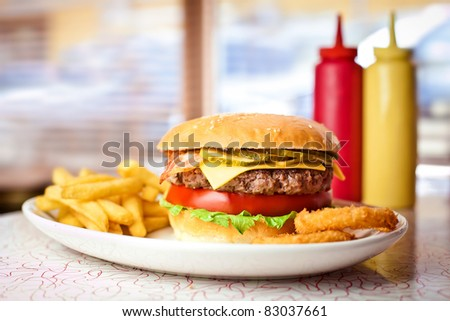 Close up of the fresh hamburger with french fries.