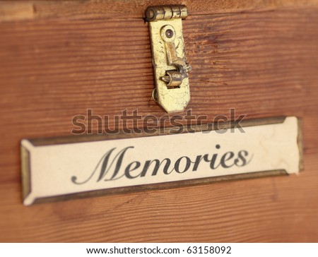 "Close up of the front of a plain, wooden box featuring a tarnished latch and label holder containing the word, ""memories.""  A narrow DOF underscores how memories fade over time."