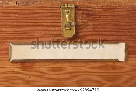 Close up of the front of a simple wooden box featuring a brass latch and label holder with a blank, yellowing label ready for your text.
