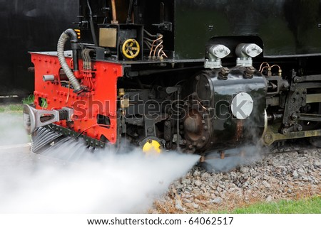 Close-up of the front of a vintage steam locomotive with steam