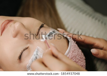 Close-up of the girl's face with closed eyes. The hand of the master applies anesthetic cream to the eyebrows before the permanent makeup procedure with a cotton swab. ストックフォト ©