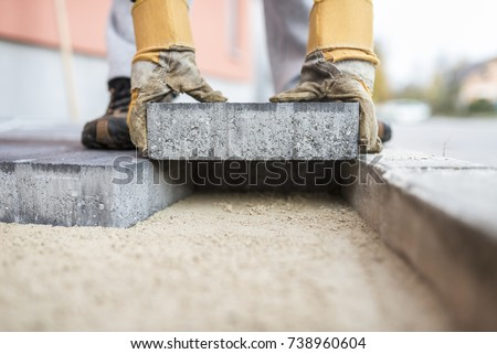 Close up of the gloved hands of a builder laying outdoor paving slabs on a prepared base.