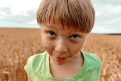 Close-up of the grimy face of a blond boy of twelve. Countryside. Happiness and fun concept.