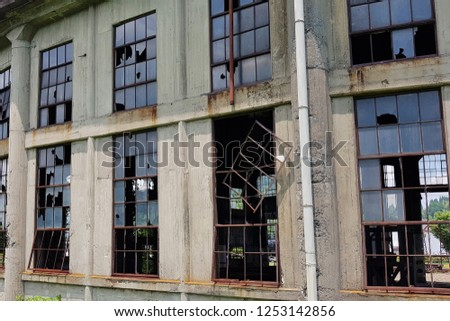 Close-up of the grunge broken windows in the old ancient steam locomotive hub building near the Bungomori Train Museum. #1253142856
