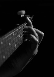 Close-up of the hand of a male guitarist on an acoustic guitarist. Musician's fingers on the strings of a guitar in black and white, a beautiful chord.