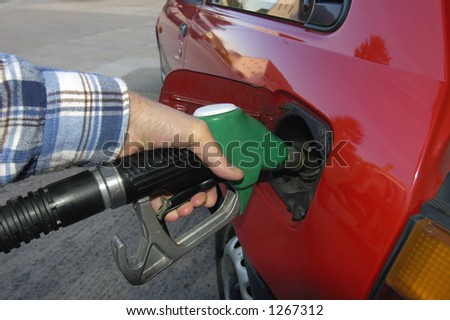 Close up of the hand of a motorist, filling his car with unleaded petrol on a garage forecourt. Beyond is the empty forecourt, but reflected in the car's bodywork is a housing estate and trees.