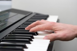 Close-up of the hand of a musical artist playing the piano, a man's hand, classical music, keyboard, synthesizer, pianist.
