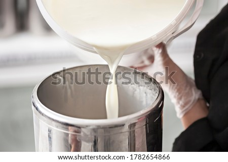 Close-up of the hand of a worker who fills fresh milk from a milk tank - Preparing Milk For Ice Cream in Modern Dairy Factory - macro photography Foto stock ©