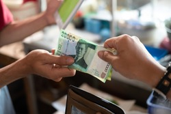 close up of the hand of an asian buyer paying in rupiah to a food stall seller after eating at a food stall