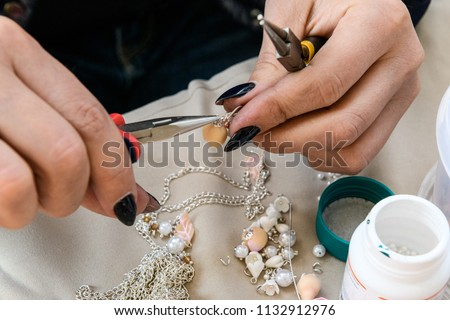 Close-up of the hand of the needlewoman who makes an ornament from beads, tightening a bead with a metal cap and a ring, using thin-nosed pliers, on her desktop with other decorating details