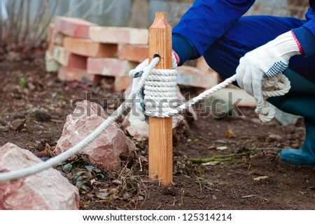 Close up of the hands decorating pale of fence with rope in the garden