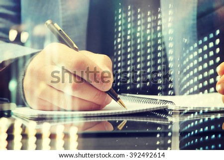 Close up of the hands of a businessman in a suit signing or writing a document  #392492614