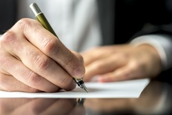 Close up of the hands of a businessman in a suit signing or writing a document on a sheet of white paper using a nibbed fountain pen