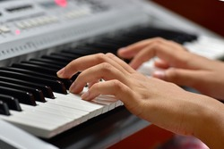 Close up of the hands of a girl playing keyboard