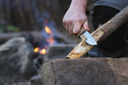 Close up of the hands of a man carving off timber to lit a fire, camp fire on the background. Hand holding knife cutting a wooden stick. Bushcraft and outdoors survival activities concept.