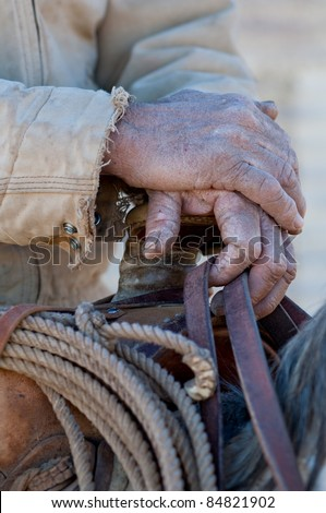 Close up of the hands of an old cowboy on his horse holding onto a saddle.
