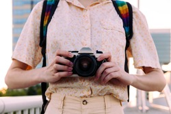 close-up of the hands with a camera of photos of an unrecognizable young tourist woman, concept of youth and traveler lifestyle