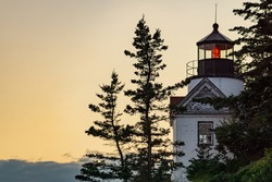 Close up of the iconic Bass Harbor Head Light Station (lighthouse) in Acadia National Park on Mount Desert Island, Maine just after sunset among a soft orange sky.