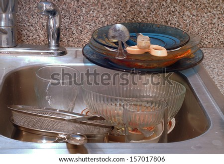 Close up of the kitchen sink with very messy piles of dirty dishes. The sink is stainless steel. The dishes are bowls, plates, pans and flatwear. Concept of disorganization and clutter and filth
