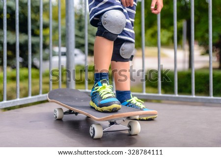 Close up of the legs of a young boy with his skateboard on a ramp dressed in colorful trainers and protective knee caps