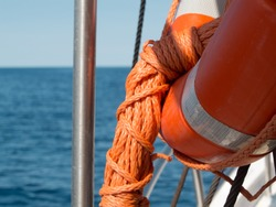 Close up of the life ring and rope elements with sea in background.