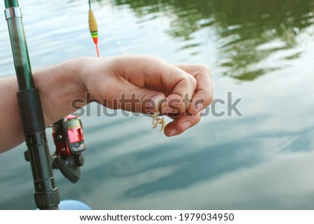 Close-up of the male hand of a fisherman, stringing maggot on the hook of a fishing rod against the backdrop of a blue river. The theme is bait for fish carp, bream, perch, crucian carp Stock photo ©